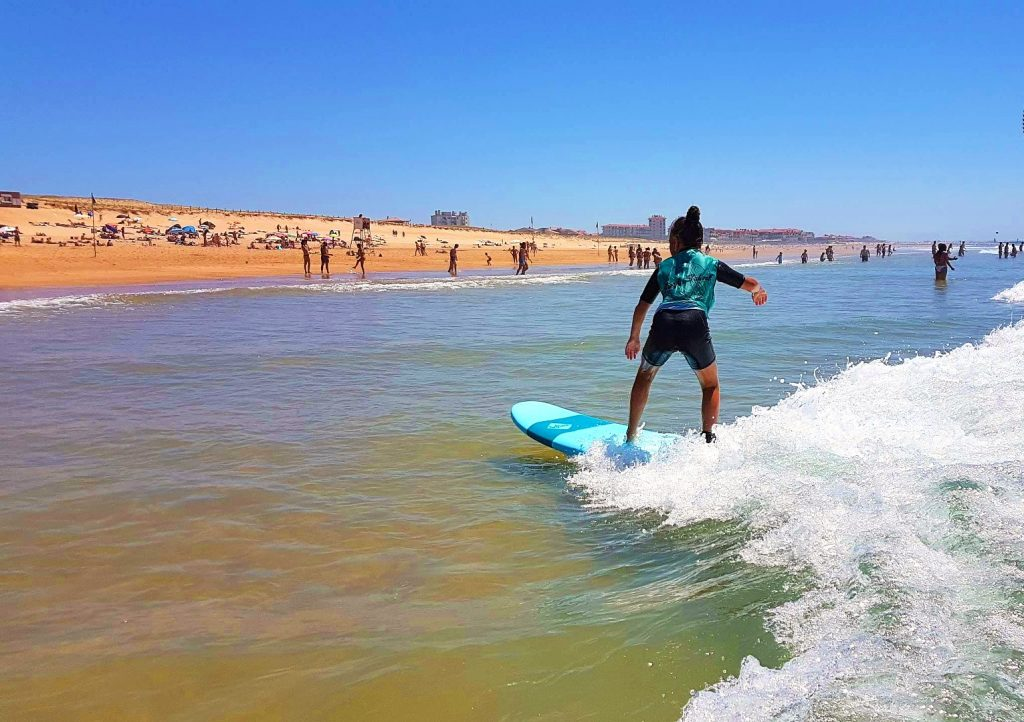 A girl is riding the waves during one of her surfing lessons in Hossegor.