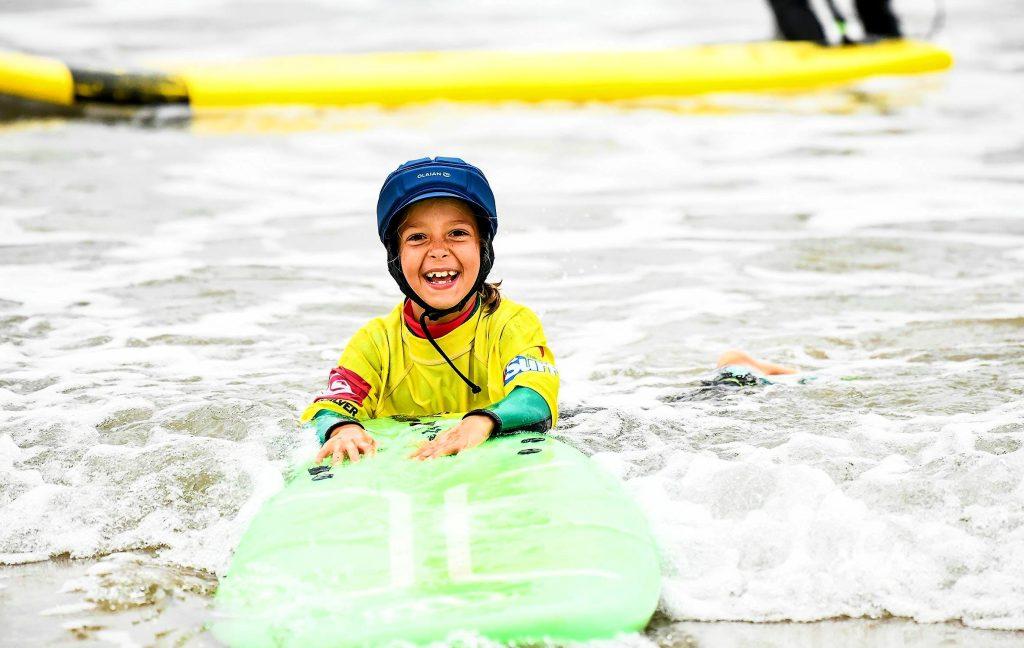 Une petite fille profite de ses cours de surf à Hendaye, le meilleur endroit pour les débutants en surf en France.