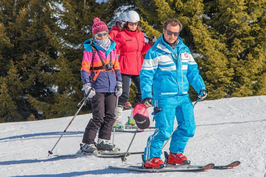 Un groupe d'adultes apprend à skier aux Gets avec l'aide d'un moniteur.