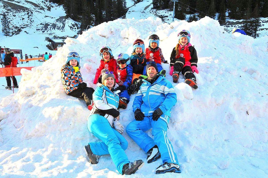 Des enfants posent pour une photo avec leurs moniteurs : l'apprentissage en groupe est le meilleur moyen d'apprendre à skier à Morzine.