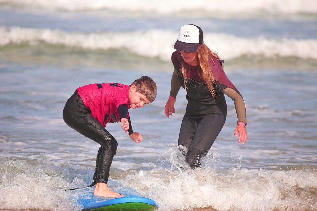 Un enfant fait du surf à Anglet encadré par son moniteur.