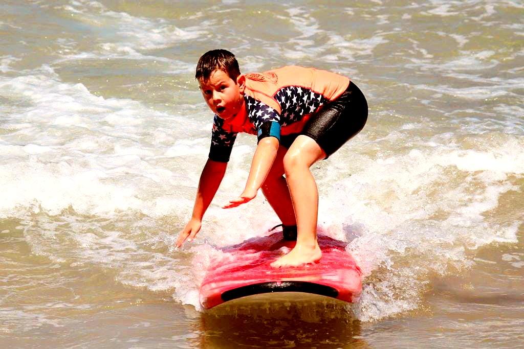 Un enfant heureux sourit pendant qu'il fait du surf à Hendaye.