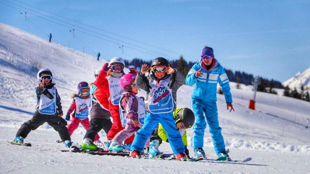 A group of children learn to ski in Les Gets with the help of an instructor.