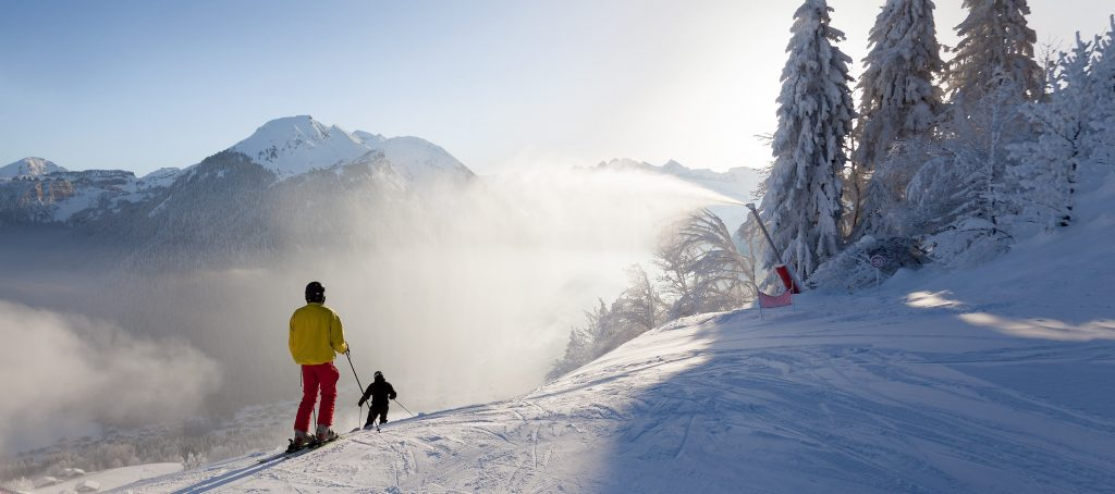 A boy learns to ski in Morzine helped by a ski instructor.