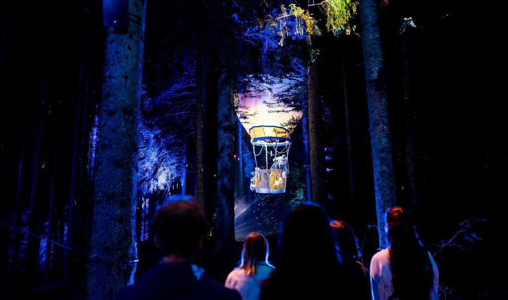 Après avoir fini d'apprendre à skier aux Gets, un groupe de gens admire le parcours nocturne Alta Lumina.