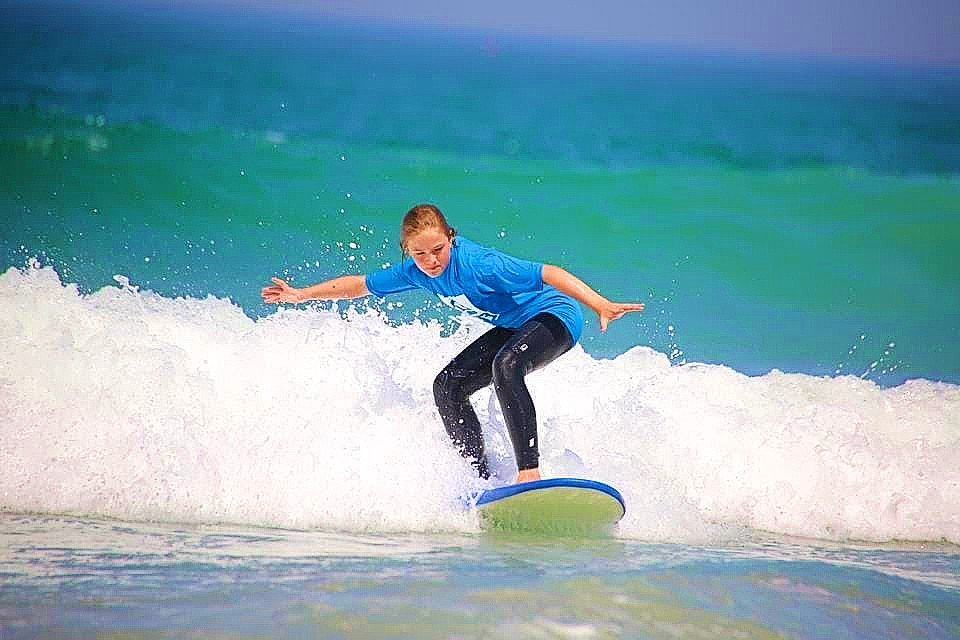 Une fille dompte une vague pendant qu'elle fait du surf à Anglet.