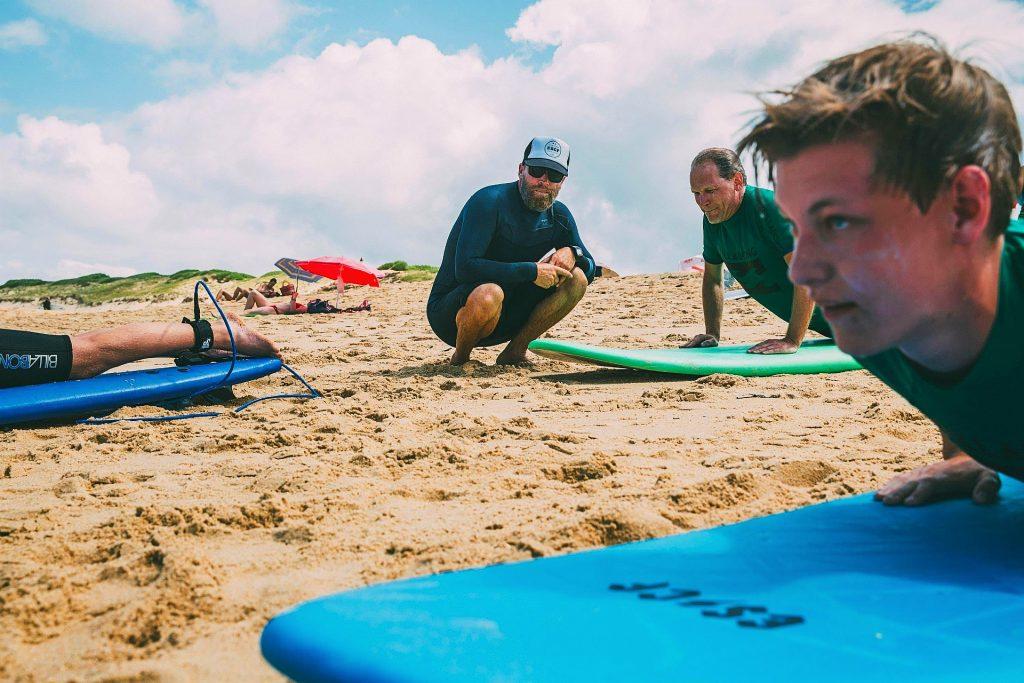 Un moniteur surveille les échauffements du groupe pendant un cours de surf à Anglet.