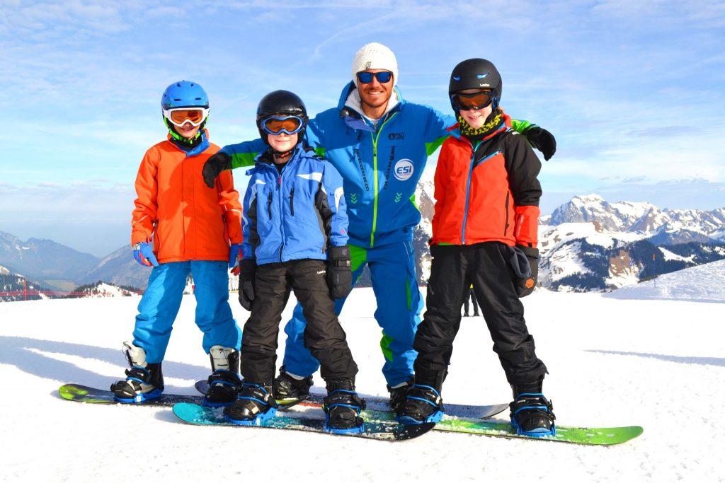 Les enfants sourient avec le moniteur de snowboard.