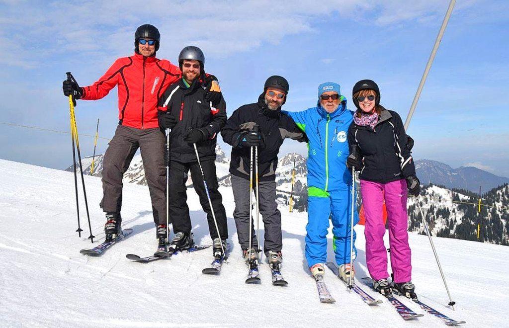Un moniteur de ski pose avec un groupe de skieurs qui veulent apprendre à skier à Châtel.