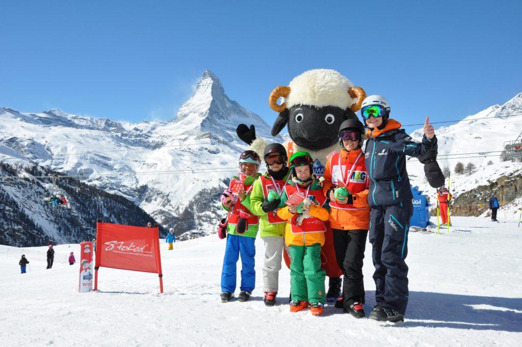 Nach einer unterhaltsamen Woche haben die Kinder das Skifahren in Zermatt gelernt und freuen sich über ihre Medaille und einen Besuch des Maskottchens.