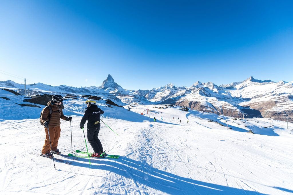 Zwei Personen stehen beim Skifahren Lernen in Zermatt auf einer fast leeren Piste.