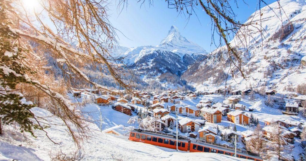 Auf dem Bild kann man Zermatt, das Matterhorn und den Zug der Gornergrat Bahn, die zu den besten Pisten zum Skifahren Lernen in Zermatt führt, bewundern.