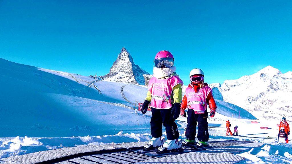 Zwei Kinder stehen beim Skifahren Lernen in Zermatt auf einem Zauberteppich.
