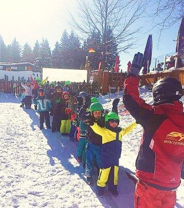 De kinderen staan in de rij en kijken naar de skileraar, iedereen staat klaar om te leren skiën in Winterberg.