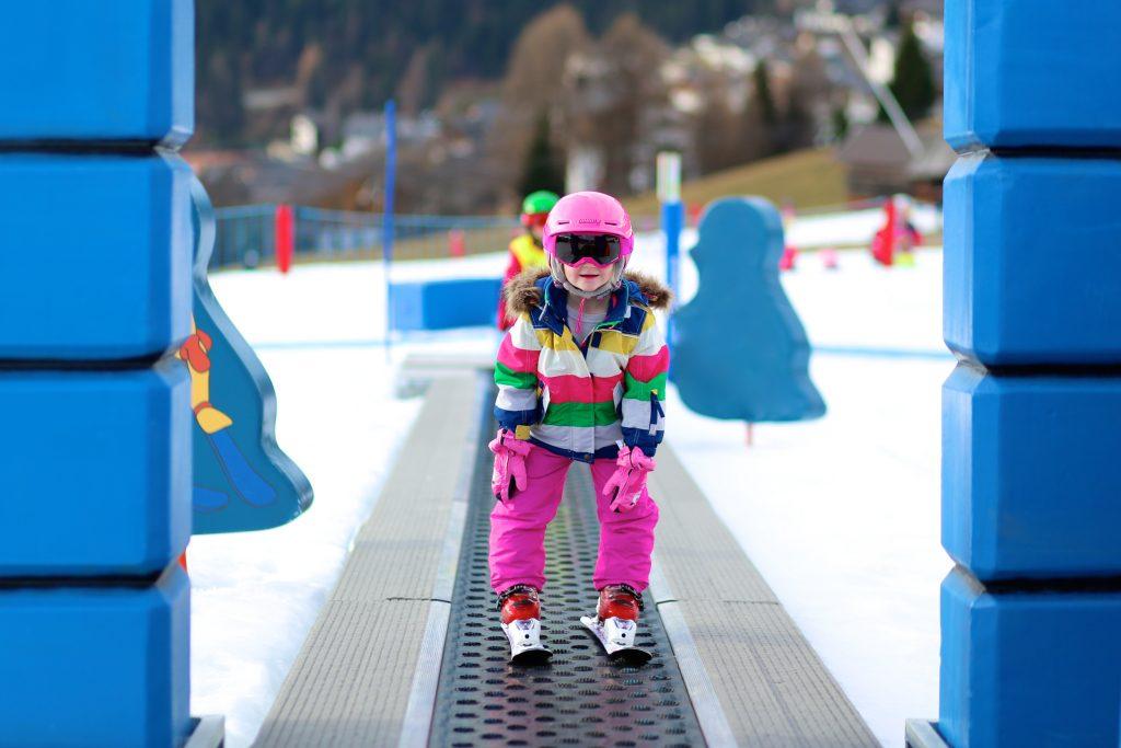 Children use the magic carpet during a ski lesson.