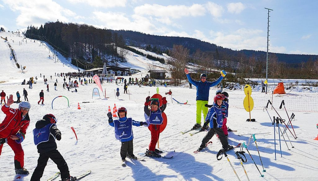 Children have fun in the kinderland while learning to ski in Winterberg.