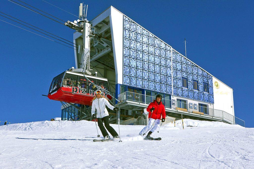 Covid-19 - Skischulen in der Schweiz: Auf den Pisten fahren zwei Personen ohne Maske, im Hintergrund die Seilbahn, wo der Mund-Nasen-Schutz obligatorisch ist.