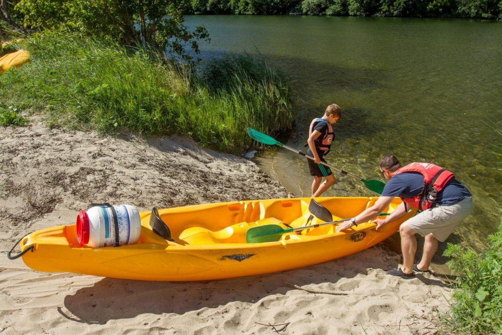 Papà e figlio rimettono la canoa in acqua dopo una pausa su una spiaggetta del fiume Ardèche.