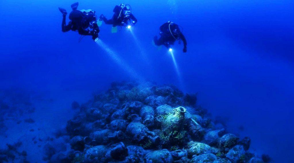 Drei Taucher bewundern die Amphoren eines antiken Schiffes, das in der Region von Zadar in der Adria gesunken ist.