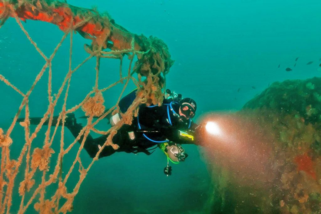 A diver is swimming past a shipwreck in Pula, and shining his flashlight at the well-preserved fishing nets.