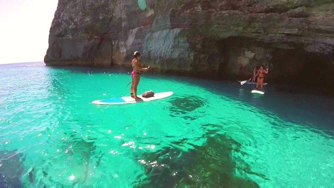 Zwei Mädchen erkunden mit dem SUP auf Malta eine Höhle.