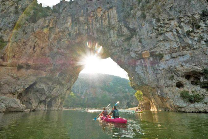 Deux personnes passent sous le Pont d'Arc lors d'une descente en canoë sur l'Ardèche.