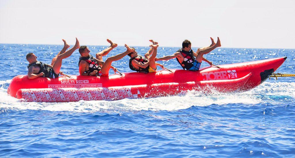 Vier Jungs haben Spaß auf einem Banana Boot auf Malta.