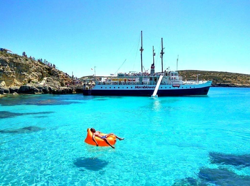 Ein Mann entspannt sich bei einer Bootstour in der blauen Lagune von Malta.