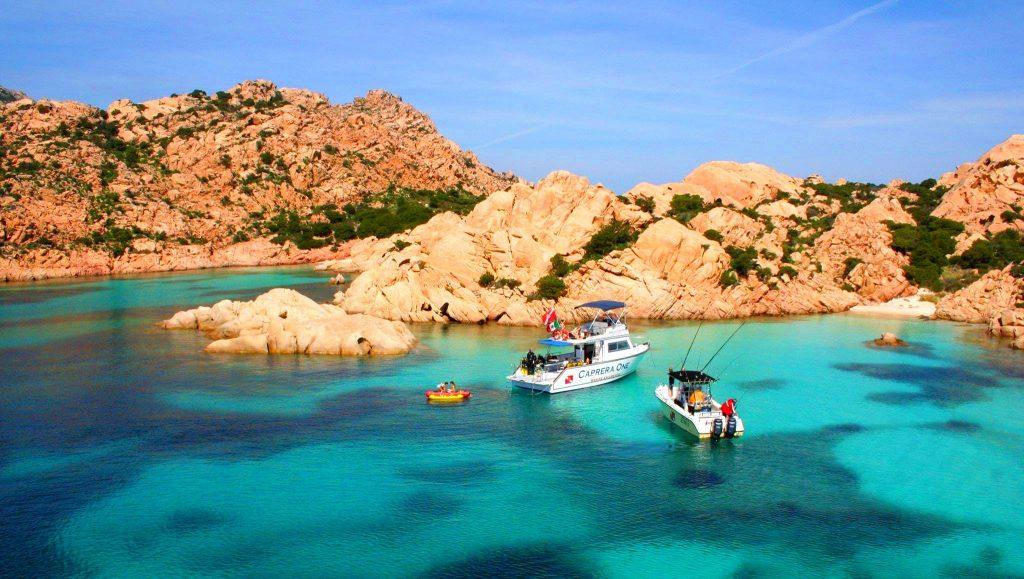 Das Boot des Orso Diving Club Poltu Quatu ist dabei, während der Bootstour zur Insel Caprera in der Nähe eines Strandes zu ankern.
