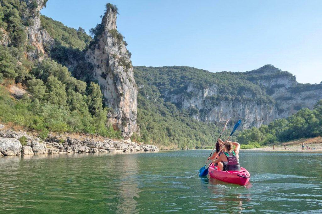 Un couple pagaie le long de la rivière lors d'une descente en canoë sur l'Ardèche.