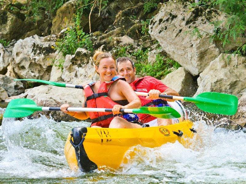 Deux personnes s'amusent pendant leur descente en canoë sur l'Ardèche.
