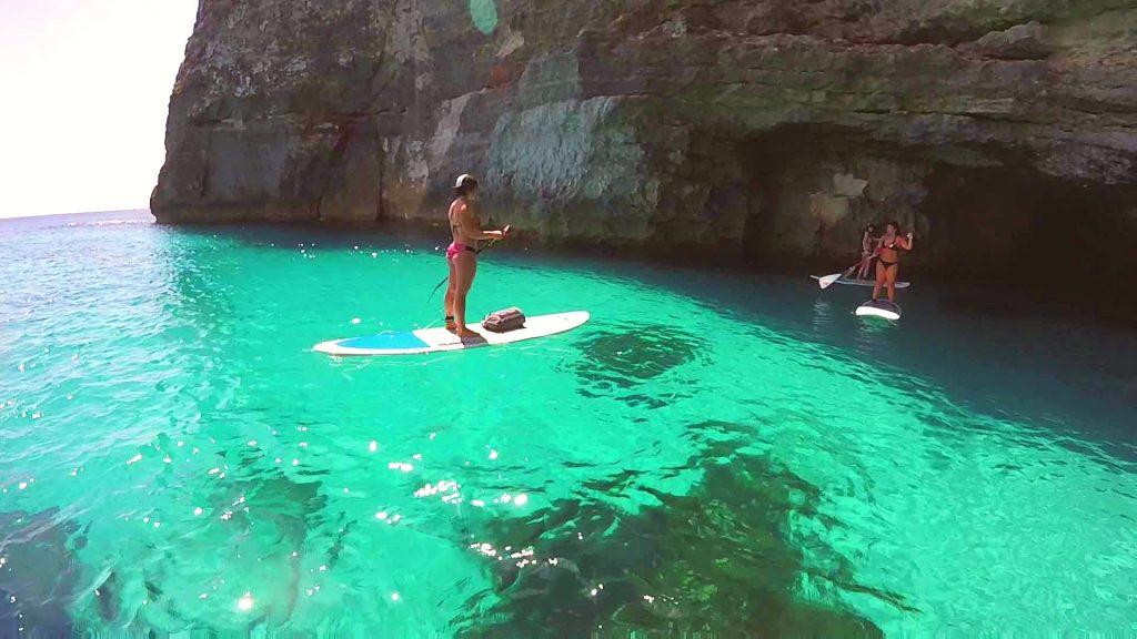 Deux jeunes femmes explorent une grotte en stand up paddle à Malte.