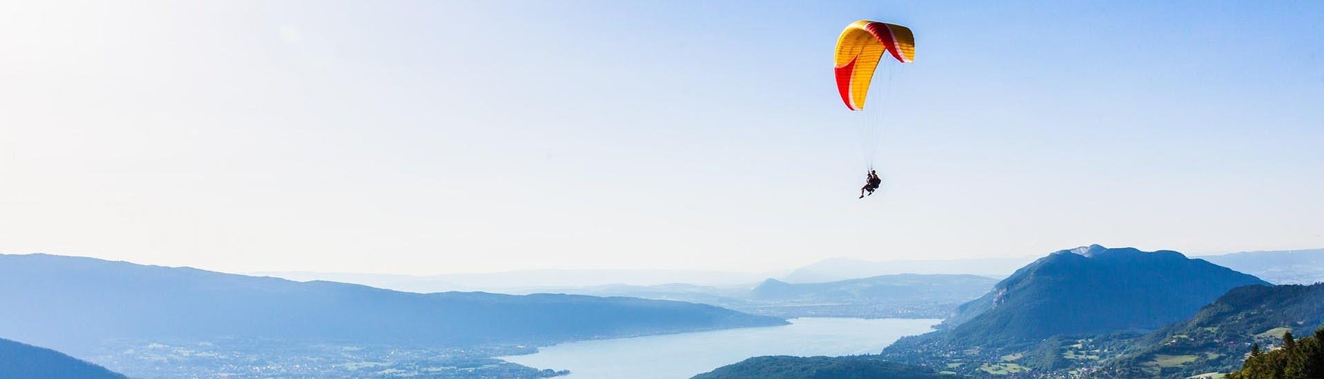 Ein Tandem-Paragleiter fliegt über den türkisblauen See von Annecy.