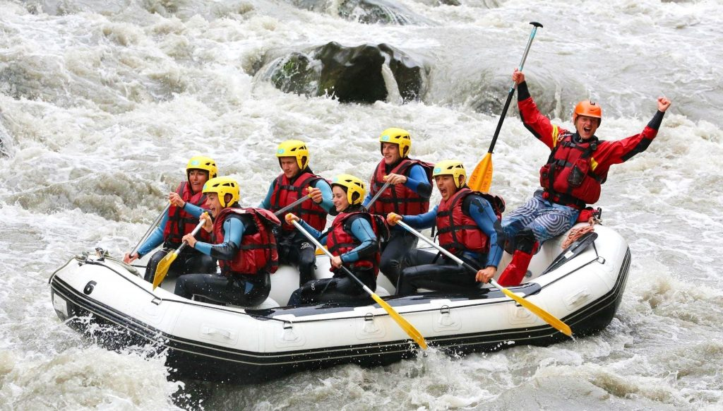 A rafting group is paddling their way through rapids.