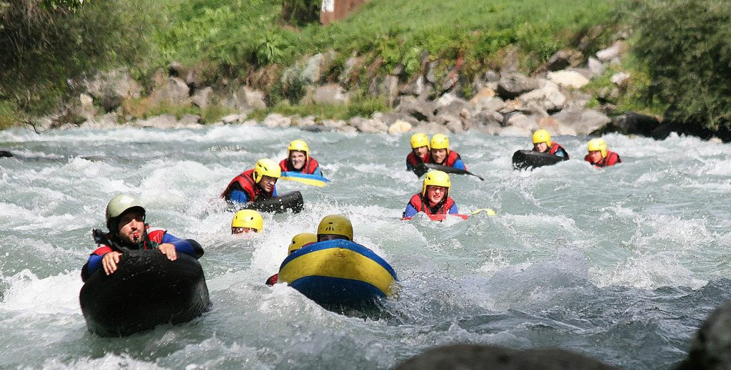 A guide and his group are swimming on their hydrospeed floaters.