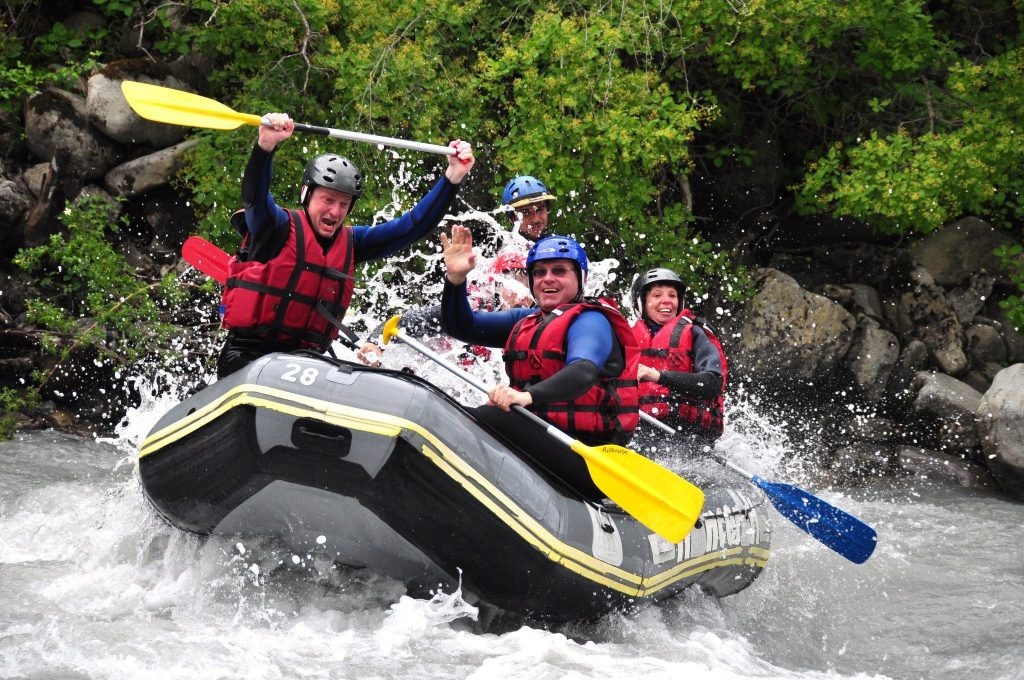 A group is going over a rapid on their raft.