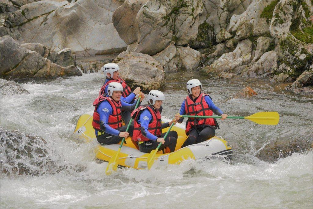 4 people are having fun on a mini raft.