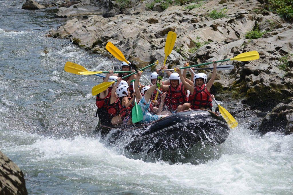 Eine Rafting-Gruppe hält ihre Paddel feierlich in die Höhe.