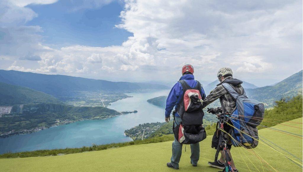 Tandem-Paragleiter bereiten sich auf ihren Flug über den See von Annecy vor.