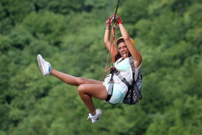 A zipline tour participant enjoys herself.