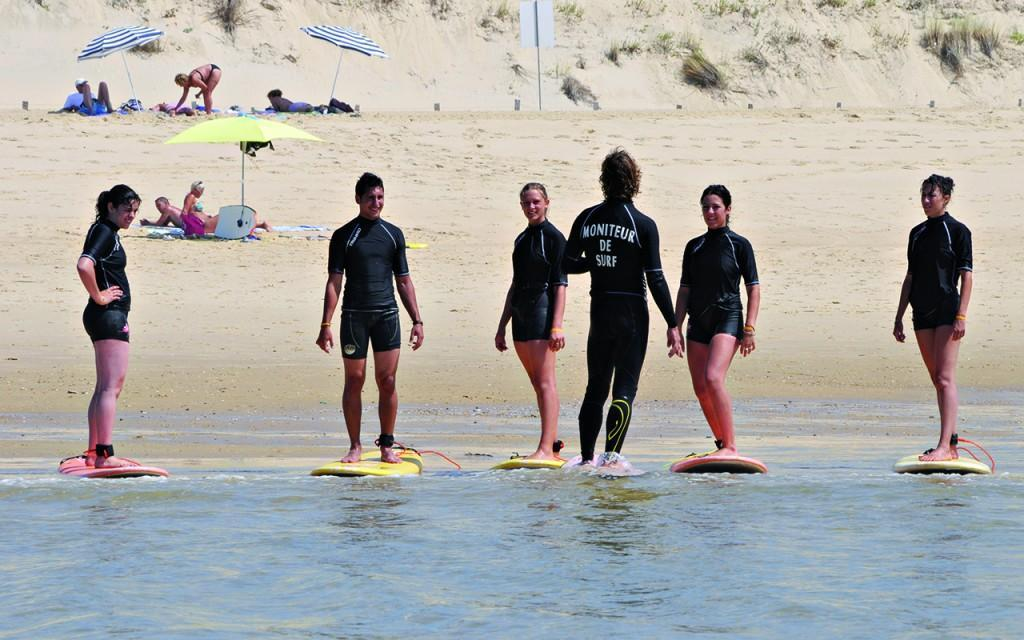 During a surf lesson for beginners, 5 participants and 1 instructor stand on the surfboard.