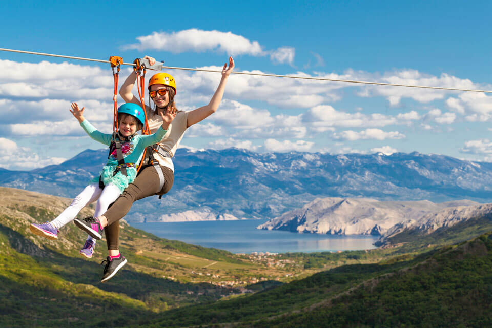 A little girl and the guide make a tandem zipline descent.