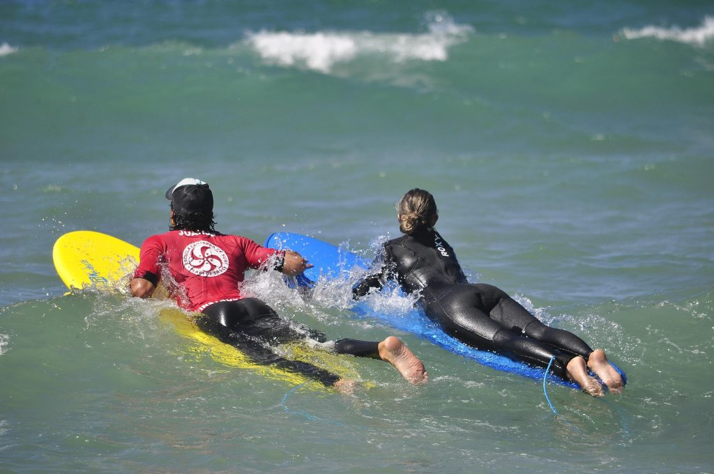 A participant in a surfing course in Spain is helped by the instructor while they are in the ocean.