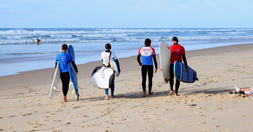 4 beginner surfers walk towards the sea.