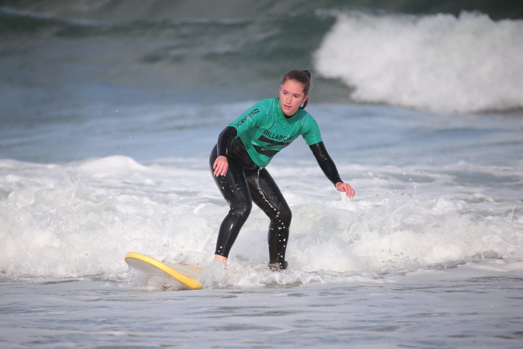 A beginner surfer standing on her surfboard riding a shallow wave.