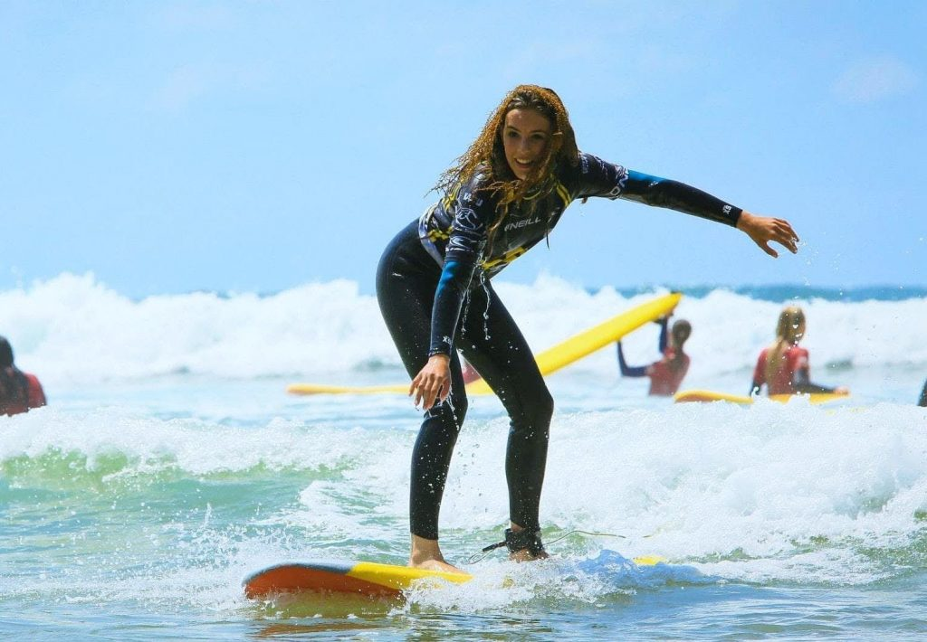 A girl, a beginner surfer, tries to balance riding a wave.