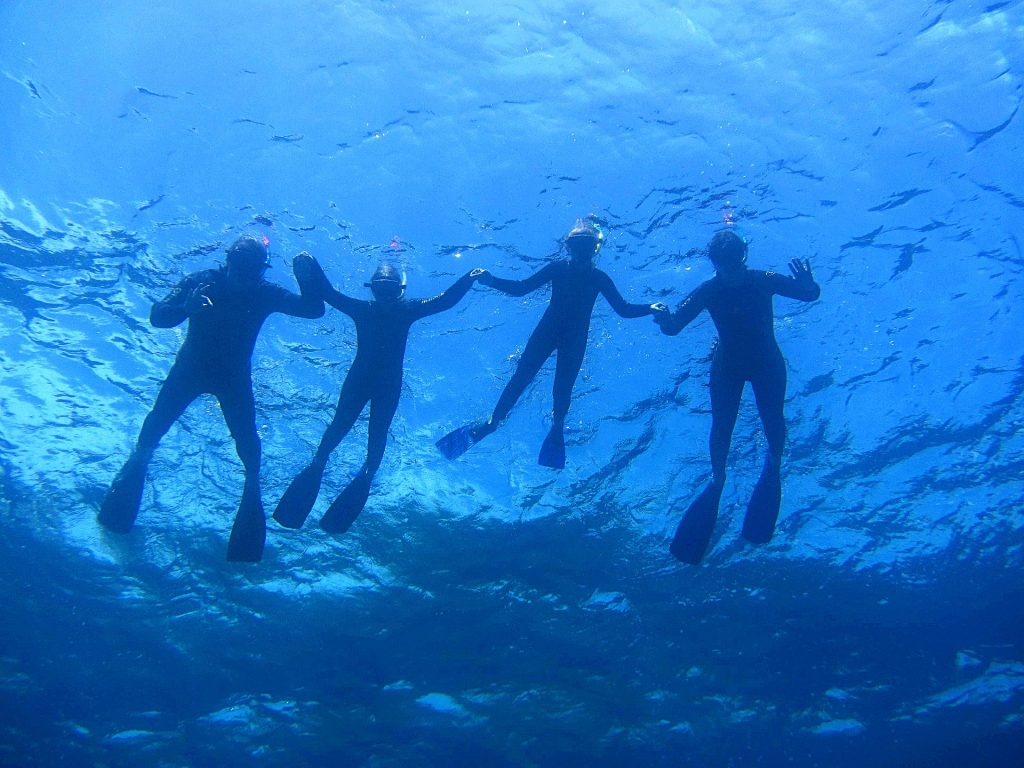Durante un'escursione di snorkeling in barca a Empros Yialo e Drepano, una famiglia fa snorkeling mentre qualcuno gli fa una foto dal basso.