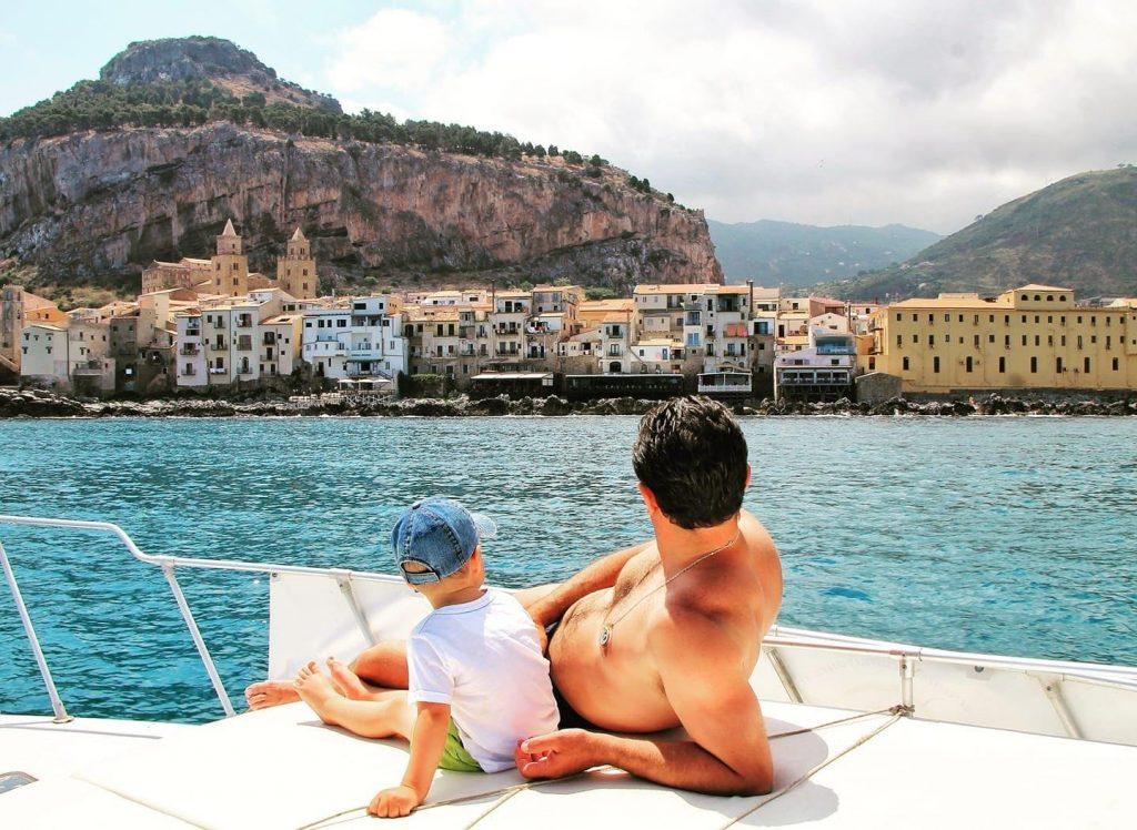 Durante una gita in barca per famiglie a Cefalù un bambino guarda la costa mentre è seduto sulla barca insieme al padre.
