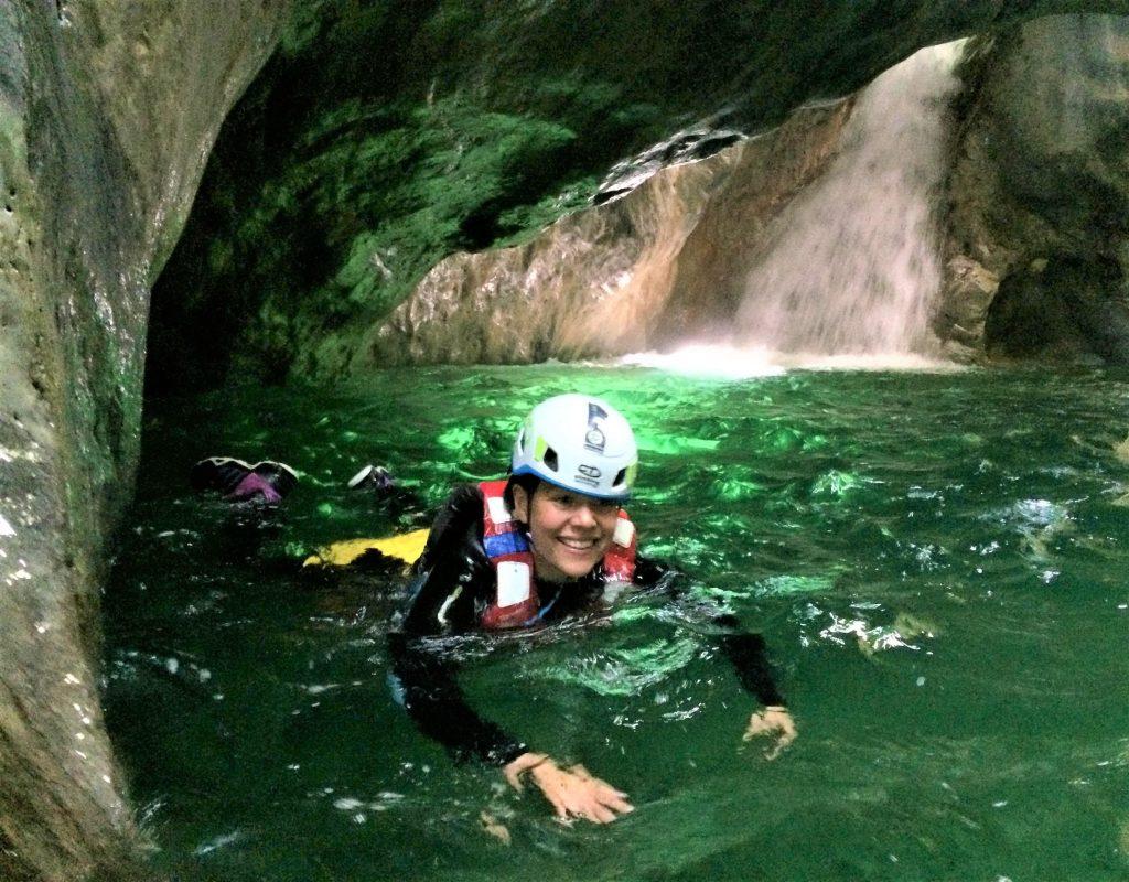 Durante il canyoning nel Palvico una ragazza nuota nella grotta.