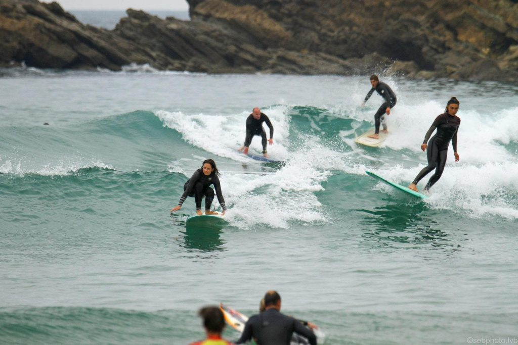 A group people train on the waves with a surfboard.